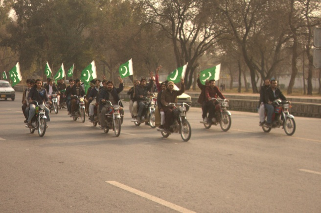 Youngsters on Bikes with Pakistani Flags marching towards Blue Area